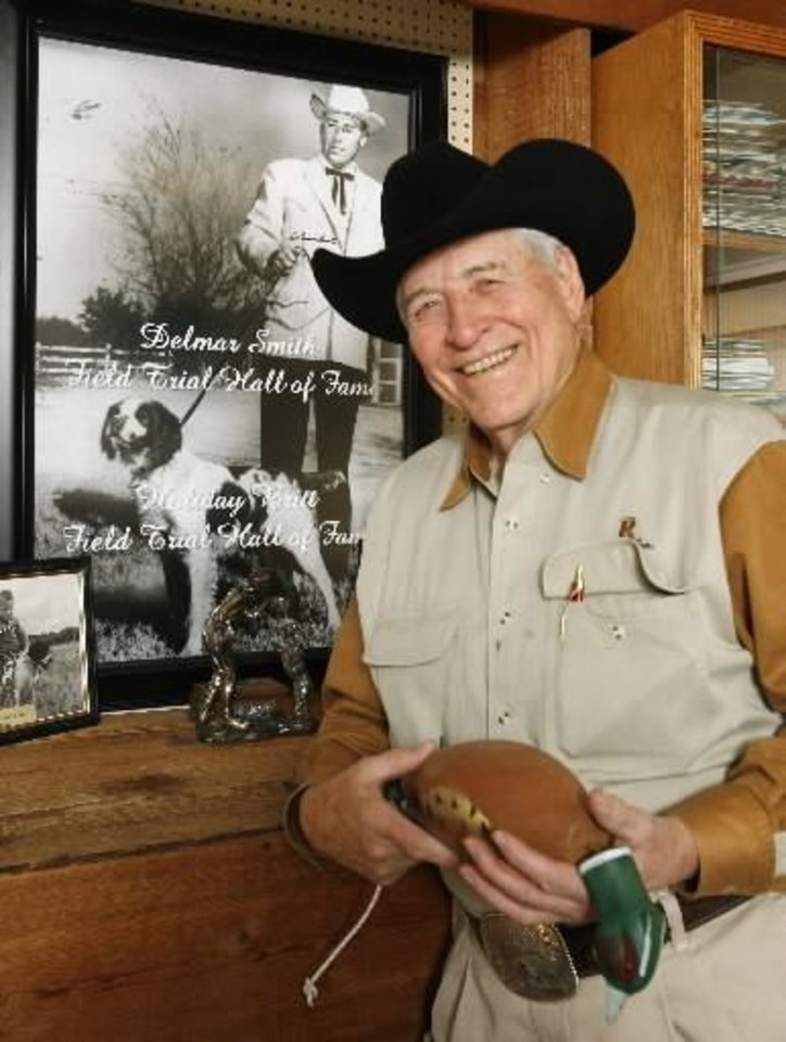 Photo - Legendary bird dog trainer  Delmar  Smith at his office in Edmond Thursday, Dec. 11, 2008. Behind is a 1960 photo of  Delmar with national champion Holiday Britt. BY PAUL B. SOUTHERLAND, THE OKLAHOMAN