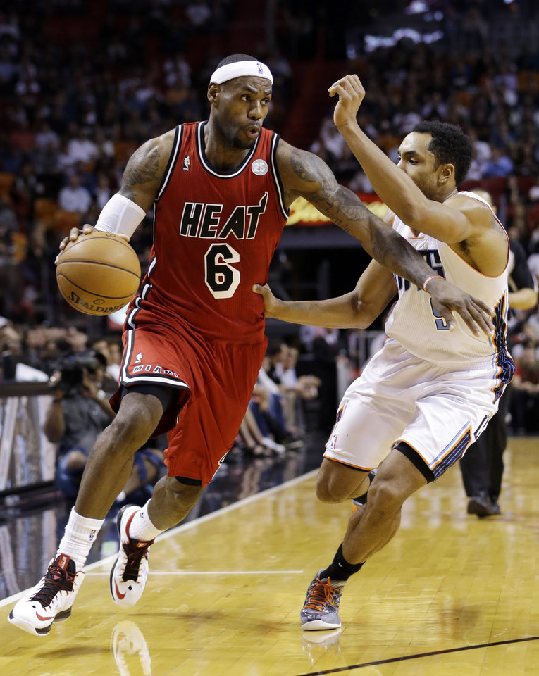 Photo - Miami Heat forward LeBron James (6) drives past Charlotte Bobcats guard Gerald Henderson during the first half of an NBA basketball game, Monday, Feb. 4, 2013 in Miami. (AP Photo/Wilfredo Lee)