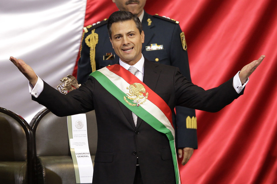 Mexico\'s incoming President Enrique Pena Nieto spreads out his arms after being sworn in at the inauguration ceremony in National Congress, in Mexico City, Saturday, Dec. 1, 2012. Pena Nieto took the oath of office as Mexico\'s new president on Saturday, bringing the old ruling party back to power after a 12-year hiatus amid protests inside and outside the congressional chamber where he swore to protect the constitution and laws of the land. (AP Photo/Alexandre Meneghini)