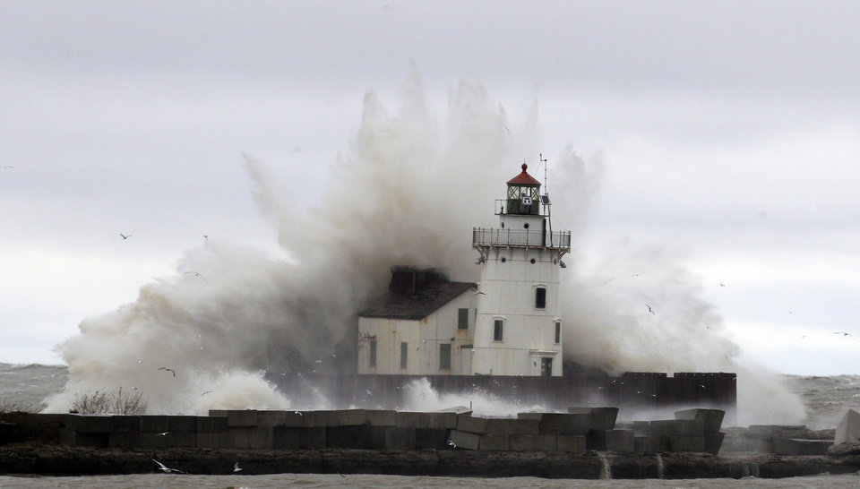 Waves pound a lighthouse on the shores of Lake Erie Tuesday, Oct. 30, 2012, near Cleveland. High winds spinning off the edge of superstorm Sandy took a vicious swipe at northeast Ohio early Tuesday, uprooting trees, cutting power to hundreds of thousands, closing schools and flooding parts of major commuter arteries that run along Lake Erie. (AP Photo/Tony Dejak) ORG XMIT: OHTD101