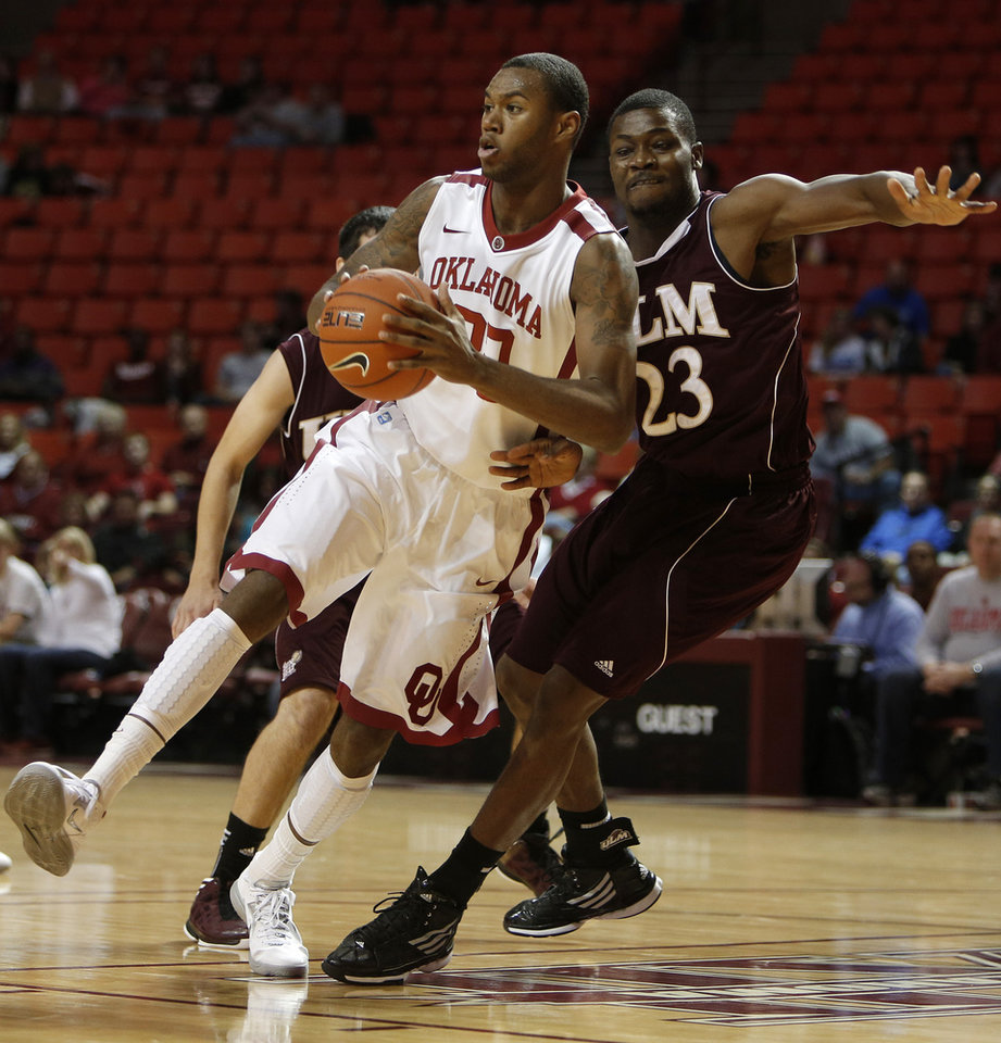 Photo - Oklahoma's Amath M'Baye (22) drives the ball past Louisiana's Millaun Brown (23) during a men's college basketball game between the University of Oklahoma and the University of Louisiana-Monroe at the Loyd Noble Center in Norman, Okla., Sunday, Nov. 11, 2012.  Photo by Garett Fisbeck, The Oklahoman