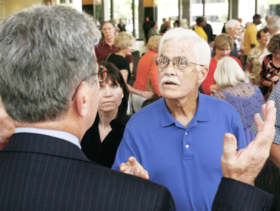Photo - An unidentified man talks to Sen. Tom Coburn on Monday after the town hall meeting in Oklahoma City.  PHOTOs BY Jim Beckel, The Oklahoman