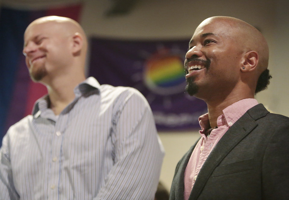 Photo - Johannes Wallmann, left, reacts to a joke told by his husband, Keith Borden, right, while speaking during Wisconsin Unites for Marriage's Marriage Bus Tour stop at the South Central LGBT Community Center in Madison, Wis., Monday, Aug. 25, 2014. The two are plaintiffs in Wolf v. Walker, challenging Wisconsin's ban on same-sex marriage. The bus continues on to Milwaukee, Racine and then Chicago Monday afternoon for a rally at Federal Plaza. On Tuesday, the 7th Circuit Court of Appeals in Chicago will hear arguments in challenges to Wisconsin and Indiana's same-sex marriage bans. (AP Photo/Wisconsin State Journal, M.P. King)