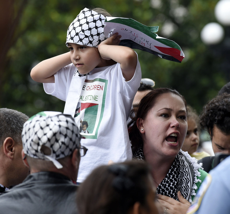 Photo - A girl covers her ears as her mother argues with pro-Israel supporters during a rally near the White House in Washington, Saturday, Aug. 2, 2014, in support of ending the violence in Gaza. A small group of Israeli supporters were surrounded by a larger group of Palestinian supporters who were protesting against the violence in Gaza. (AP Photo/Susan Walsh)