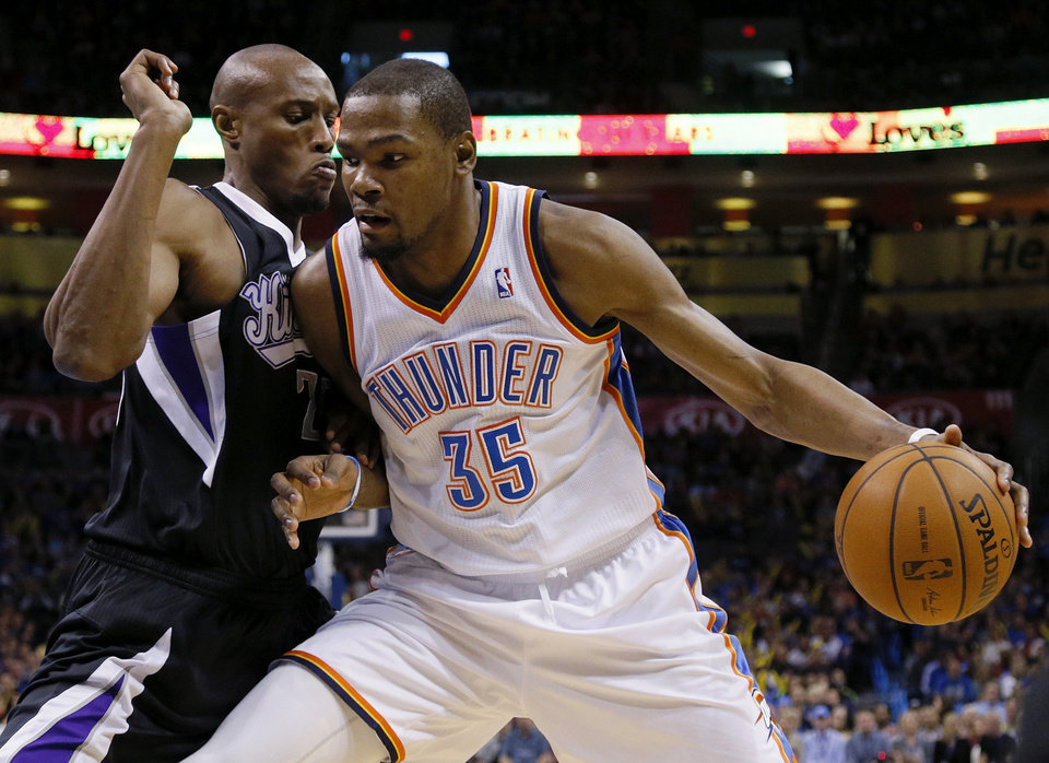 Photo - Oklahoma City's Kevin Durant (35) tries to get past Sacramento's Travis Outlaw (25) during an NBA game between the Oklahoma City Thunder and the Sacramento Kings at Chesapeake Energy Arena in Oklahoma City, Friday, March 28, 2014. Photo by Bryan Terry, The Oklahoman
