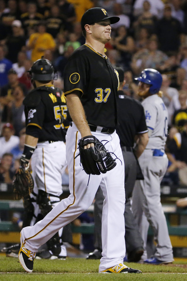 Photo - Pittsburgh Pirates relief pitcher Justin Wilson (37) walks off the field after being ejected for hitting Los Angeles Dodgers' Justin Turner, right rear, with a pitch during the seventh inning of a baseball game in Pittsburgh Tuesday, July 22, 2014. (AP Photo)