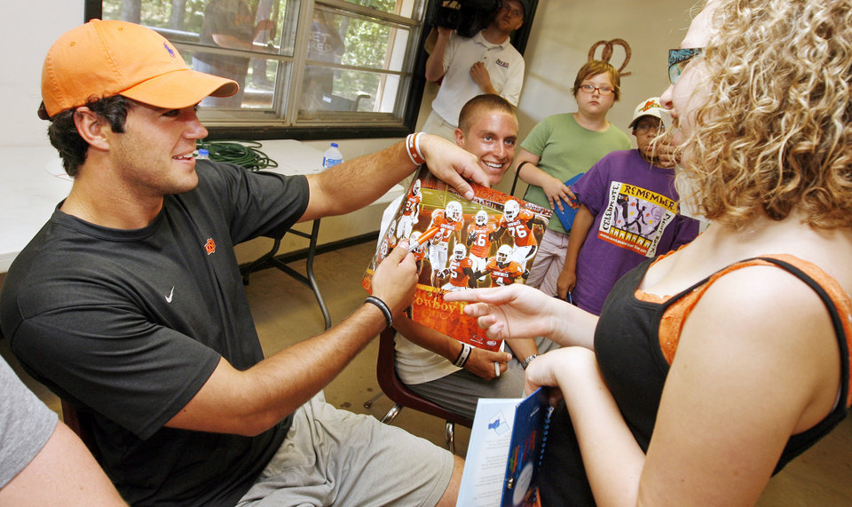Photo - Oklahoma State quarterback Zac Robinson quizes camper Brylea Lind, 14, on where Robinson is on an OSU poster before signing an autograph for Lind at the American Cancer Society's Camp Live-A-Dream in Guthrie, Okla., Wednesday, June 17, 2009. Looking on to the right of Robinson is OSUs Taylor Sokolosky. Photo by Nate Billings, The Oklahoman