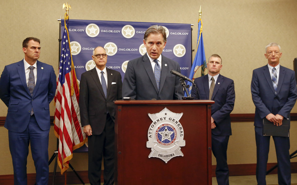 Photo - Oklahoma Attorney General Mike Hunter, center, speaks in front of, from left, Gov. Kevin Stitt, Rep. Harold Wright, Rep. Chris Kannady and Department of Corrections Director Scott Crow during a press conference announcing plans for Oklahoma to resume executions by lethal injection, at the Office of the Attorney General, 313 NE 21, in Oklahoma City, Thursday, Feb. 13, 2020. [Nate Billings/The Oklahoman]