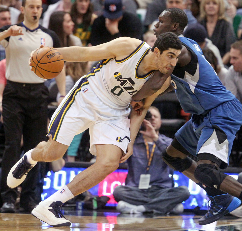 Photo - Utah Jazz's Enes Kanter (0) drives against Minnesota Timberwolves' Gorgui Dieng (5) in the second quarter of an NBA basketball game Saturday Feb. 22, 2014, in Salt Lake City. (AP Photo/Rick Bowmer)
