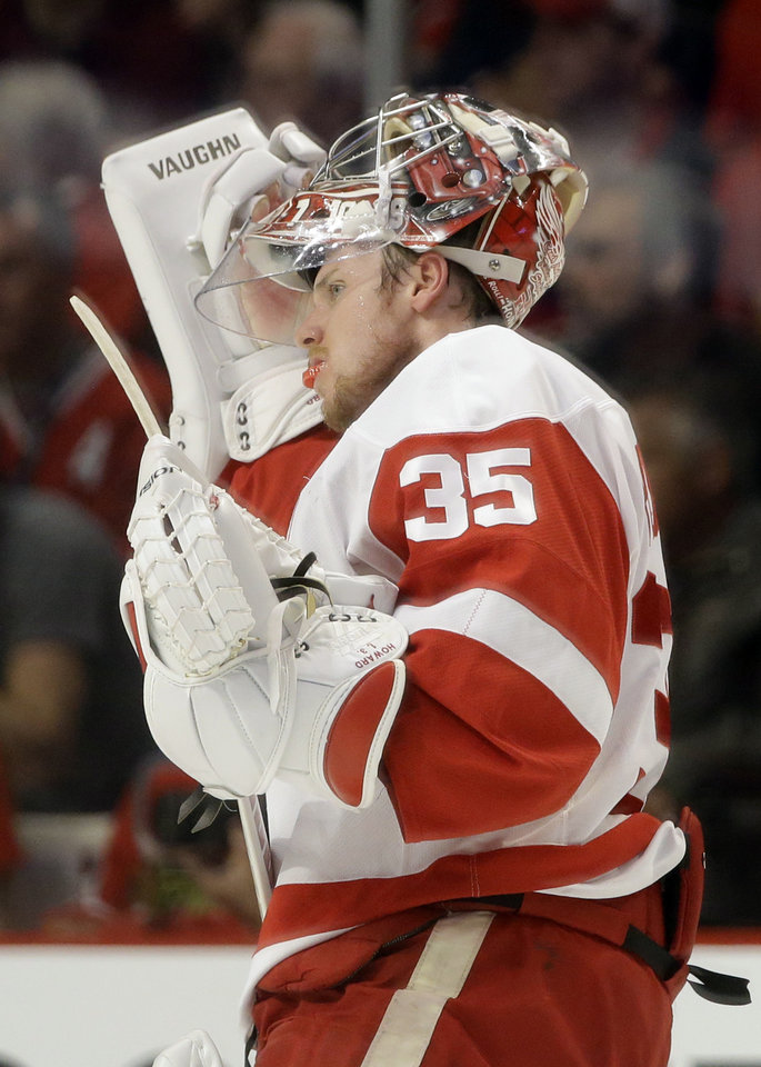 Photo - Detroit Red Wings goalie Jimmy Howard adjusts his facemask during the first period of Game 2 of the NHL hockey Stanley Cup playoffs Western Conference semifinals against the Chicago Blackhawks Saturday, May 18, 2013, in Chicago. (AP Photo/Nam Y. Huh)
