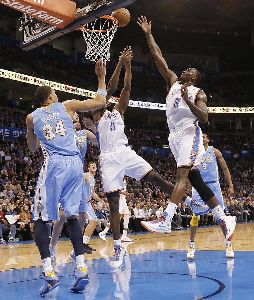 Photo - Oklahoma City's Kendrick Perkins (5) puts a shot up over Denver's JaVale McGee (34) during the NBA basketball game between the Oklahoma City Thunder and the Denver Nuggets at the Chesapeake Energy Arena on Wednesday, Jan. 16, 2013, in Oklahoma City, Okla.  Photo by Chris Landsberger, The Oklahoman