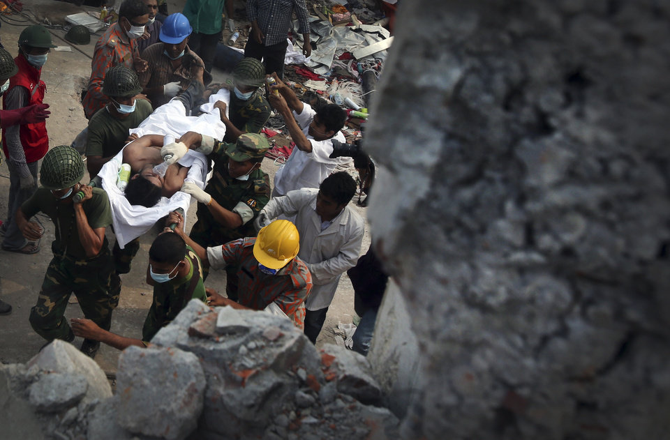Photo - A survivor is evacuated from a garment factory building that collapsed Wednesday in Savar, near Dhaka, Bangladesh, Saturday, April 27, 2013. Police in Bangladesh took five people into custody in connection with the collapse of a shoddily-constructed building this week, as rescue workers pulled 19 survivors out of the rubble on Saturday and vowed to continue as long as necessary to find others despite fading hopes.(AP Photo/Wong Maye-E)
