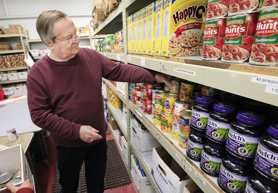 Photo -      Volunteer Steve Cunningham sorts donated canned goods at the HOPE Center in Edmond. Photos by Paul B. Southerland, The Oklahoman   PAUL B. SOUTHERLAND -