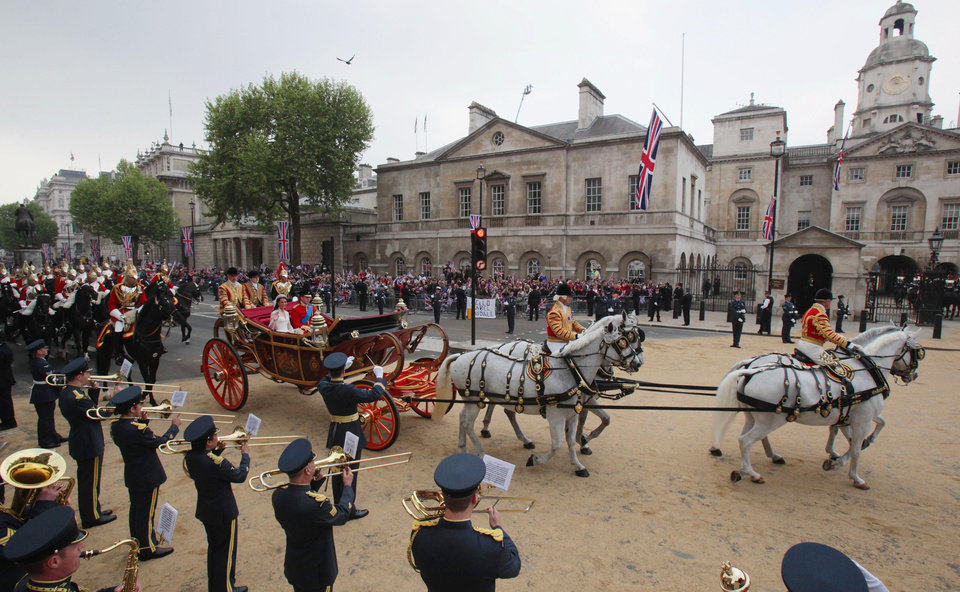 Photo - Britain's Prince William and Kate, the Duchess of Cambridge, wave as they travel in the 1902 State Landau carriage along the processional route to Buckingham Palace, London, Friday April 29, 2011. (AP Photo/Matt Cardy, Pool)  ORG XMIT: GYI0064508923.JPG