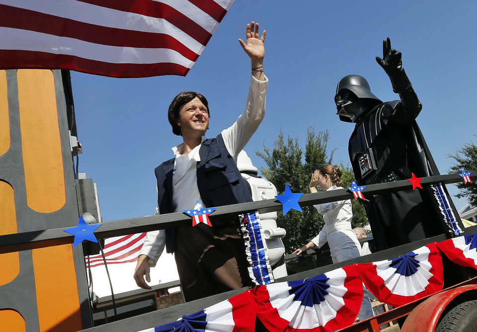 Photo - Star Wars characters, including Han Solo, left, and Darth Vader, wave from the JediOKC float during the Edmond LibertyFest Parade in downtown Edmond, Okla., on Independence Day, Friday, July 4, 2014. Photo by Nate Billings, The Oklahoman