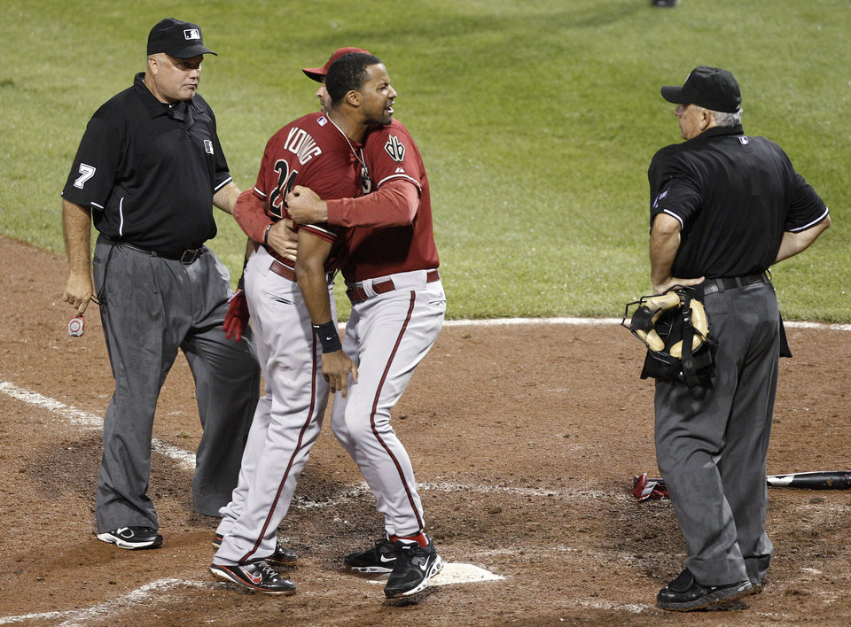 Photo -   Arizona Diamondbacks' Chris Young, center left, is restrained by manager Kirk Gibson, center right, as he argues with home plate umpire Larry Vanover, right, after being ejected for arguing a called third strike for the last out in the of the top of the seventh inning of the baseball game against the Pittsburgh Pirates, Wednesday, Aug. 8, 2012, in Pittsburgh. First base umpire Alfonso Marquez is at left. The Pirates won 7-6. (AP Photo/Keith Srakocic)