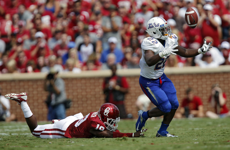 Photo - Tulsa 's Trey Watts (22) makes a catch in front ofOklahoma's Eric Striker (19) during the college football game between the University of Oklahoma Sooners (OU) and the University of Tulsa Hurricanes (TU) at the Gaylord-Family Oklahoma Memorial Stadium on Saturday, Sept. 14, 2013 in Norman, Okla.  Photo by Chris Landsberger, The Oklahoman