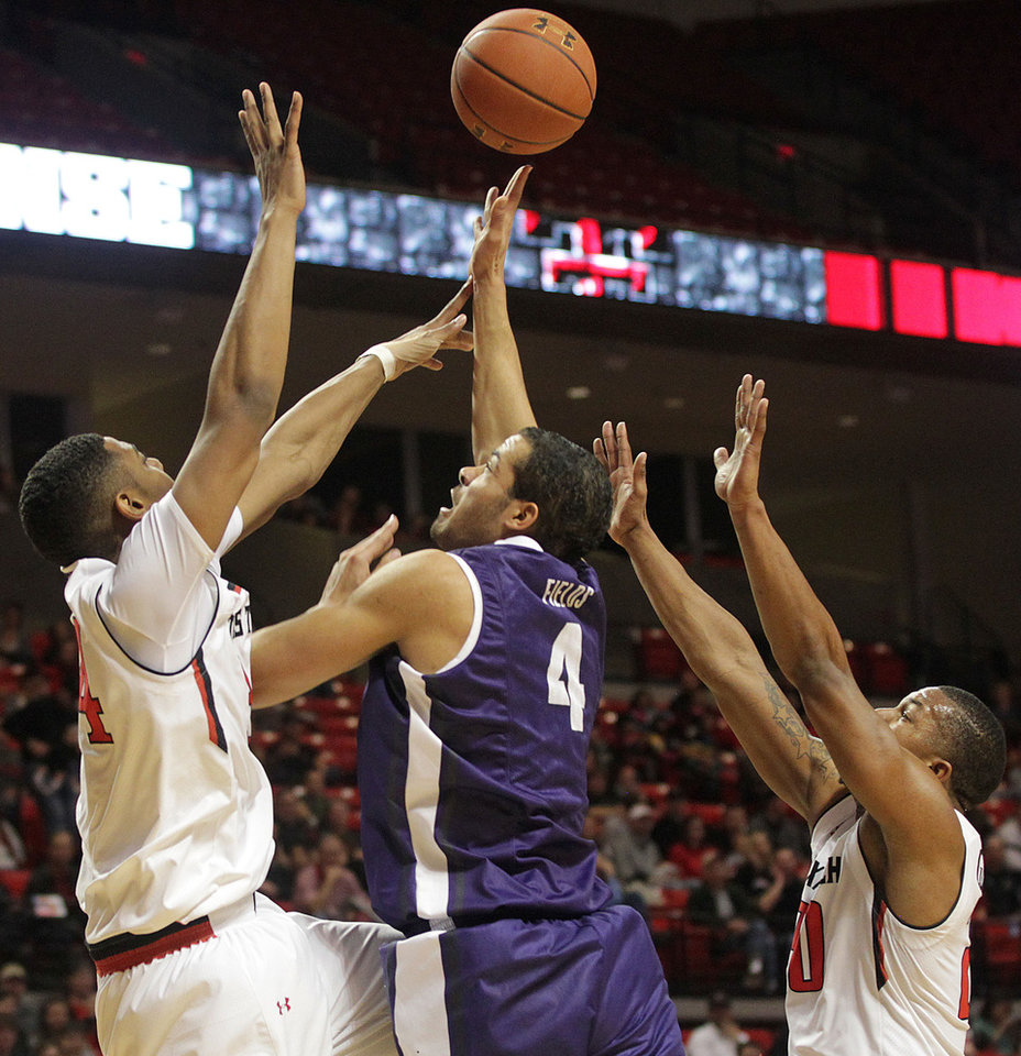 Photo - TCU's Amric Fields shoots around Texas Tech's Alex Foster, left, and Toddrick Gotcher during an NCAA college basketball game in Lubbock, Texas, Saturday, Feb, 1, 2014. (AP Photo/Lubbock Avalanche-Journal, Tori Eichberger) LOCAL TV OUT