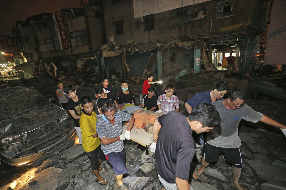 Photo - The body of a victim killed in a gas explosion from an underground gas leak is carried from the rubble in a main street in Kaohsiung, Taiwan, early Friday, Aug. 1, 2014.  A massive gas leakage early Friday caused five explosions that killed several people and injured over 200 in the southern Taiwan port city of Kaohsiung. (AP Photo)  TAIWAN OUT