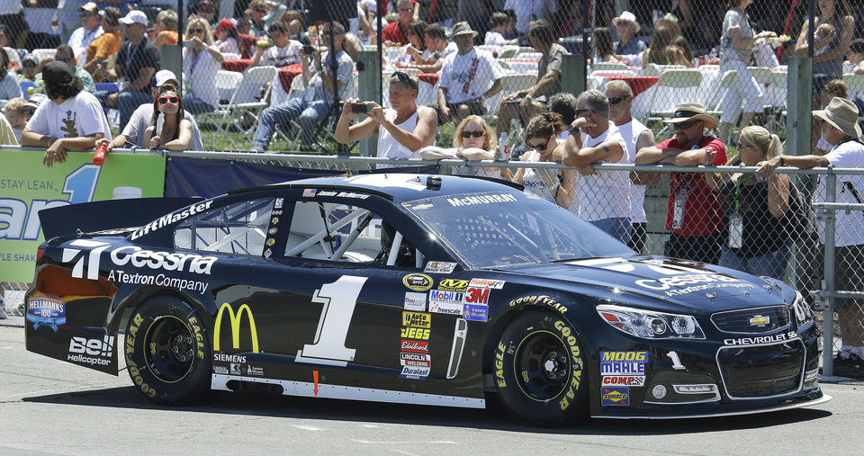 Photo - Jamie McMurray leaves the track after qualifying for the pole position in the NASCAR Sprint Cup series auto race Saturday, June 22, 2013, in Sonoma, Calif. (AP Photo/Ben Margot)