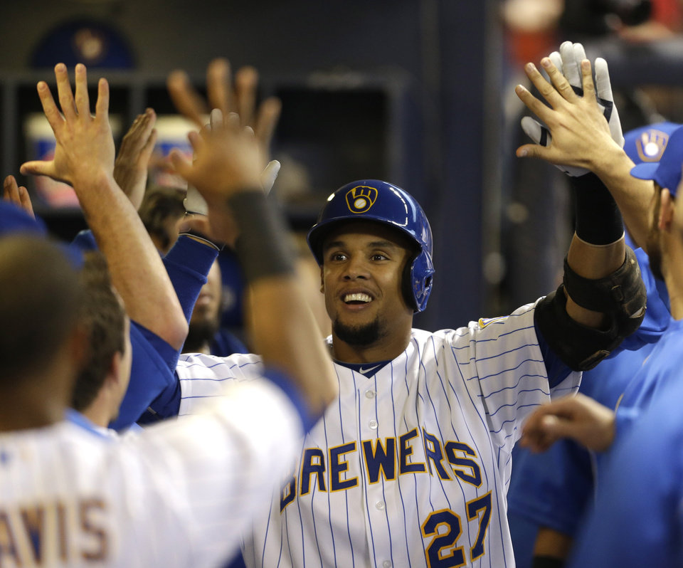 Photo - Milwaukee Brewers' Carlos Gomez reacts in the dugout after his home run off Pittsburgh Pirates starting pitcher Edinson Volquez during the first inning of a baseball game Saturday, April 12, 2014, in Milwaukee. (AP Photo/Jeffrey Phelps)