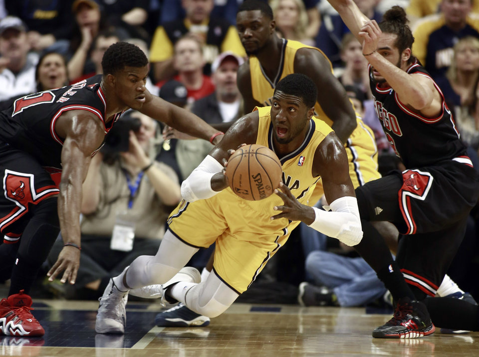 Photo - Indiana Pacers center Roy Hibbert passes the basketball while falling as Chicago Bulls guard Jimmy Butler, left, and center Joakim Noah, right, defend during the first half of an NBA basketball game in Indianapolis, Friday, March 21, 2014. (AP Photo/R Brent Smith)