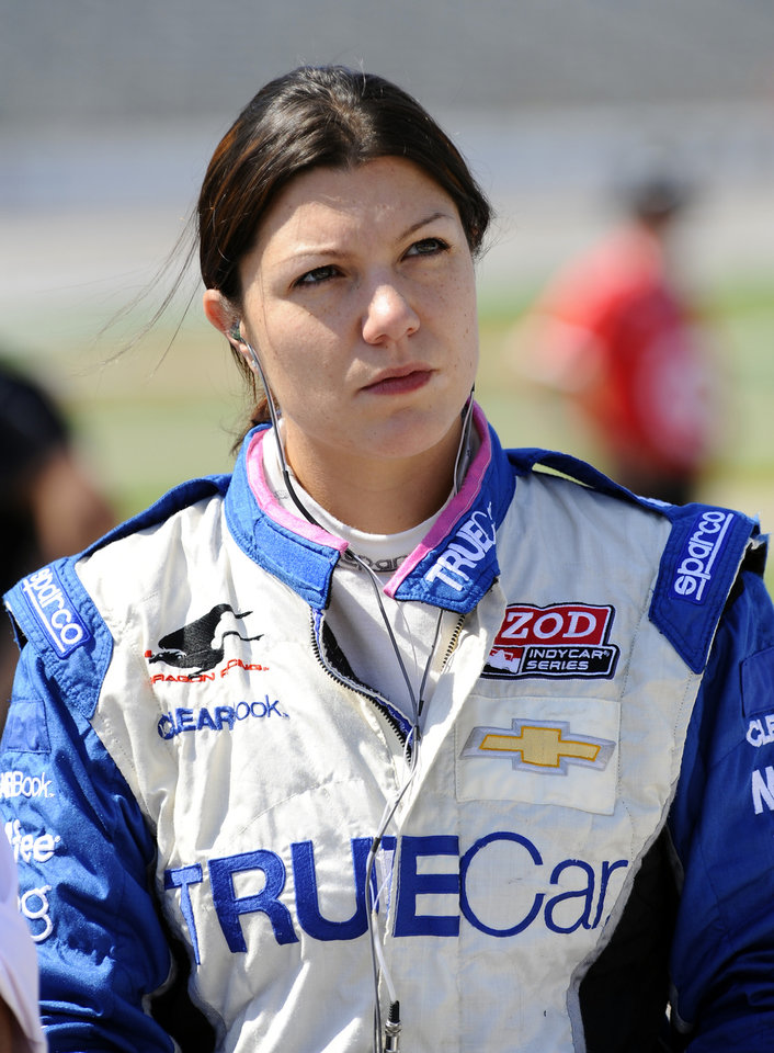Photo - FILE - In this June 8, 2012, file photo, driver Katherine Legge watches before IndyCar Series qualifying at Texas Motor Speedway in Fort Worth, Texas. Legge has threatened legal action over her termination from Dragon Racing on Wednesday, Feb. 13, 2013, one day after the team said Sebastian Saavedra had been hired to drive the No. 6 this IndyCar season. (AP Photo/Ralph Lauer, File)