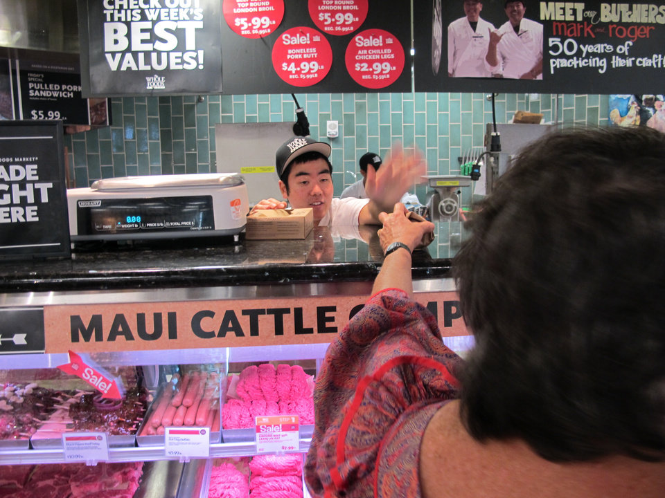 Photo -   Dean Jitchaku, an apprentice meat cutter, hands a package of grass-fed beef to a customer at the Whole Foods Market Kahala store in Honolulu on Sept. 28, 2012. National trends in locally grown foods and grass-fed beef have caught on in Hawaii, but crushing drought has made it difficult for ranchers to keep enough cattle in Hawaii to capitalize on the demand. (AP Photo/Audrey McAvoy)