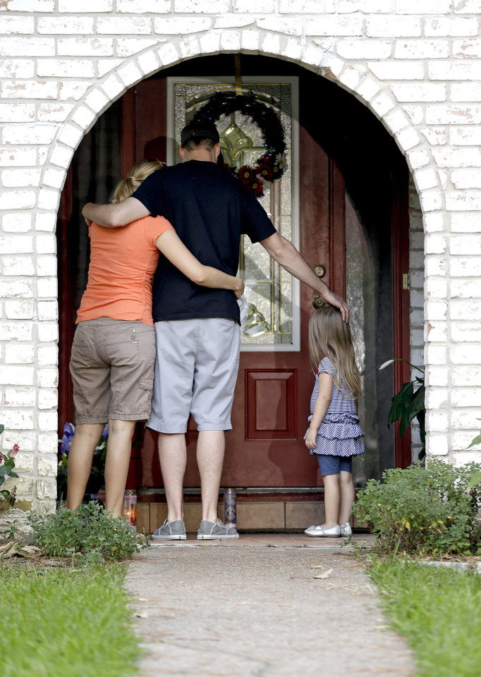 Photo - A family who identified themselves as friends of the victims, pause on the porch Thursday, July 10, 2014, after placing flowers and a framed photograph at the door of the home where a gunman killed six people Wednesday in Spring, Texas. The Harris County Sheriff?s Office says Ronald Lee Haskell was booked Thursday on a capital murder/multiple murders charge and held without bond. Authorities believe Haskell fatally shot two adults and four children on Wednesday night and critically wounded a 15-year-old girl, who called 911. (AP Photo/David J. Phillip)