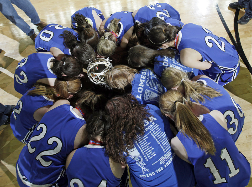 The Lomega Raiderettes kneel around the gold ball championship trophy to pray after the Class B state championship girls high school basketball game between Hammon and Lomega at State Fair Arena in Oklahoma City, Saturday, March 3, 2012. Lomega won, 49-44. Photo by Nate Billings, The Oklahoman
