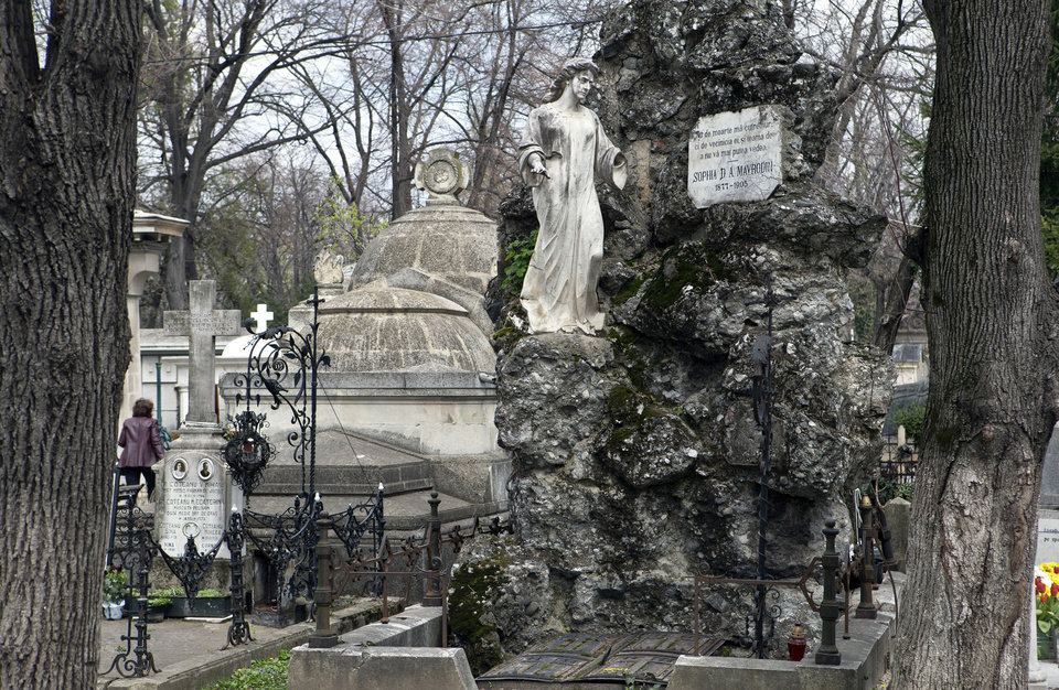 This April 10, 2013 photo shows a statue decorating a grave at the Bellu cemetery in Bucharest, Romania. It was founded by a shepherd, according to local legend, and was later nicknamed the Paris of the East. But Bucharest's idyllic roots and elegant reputation eventually gave way to a series of 20th century calamities: war, invasions, earthquakes and communism.(AP Photo/Vadim Ghirda)