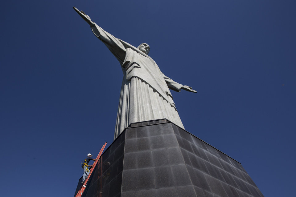 Photo - A worker climbs the Christ Redeemer statue to examine recent damage in Rio de Janeiro, Brazil, Tuesday, Jan. 21, 2014. The famed statue is being examined after two fingers and the head were chipped during recent lightning storms. Officials say they'll place more lightning rods on the statue in an effort to prevent future damage. (AP Photo/Felipe Dana)