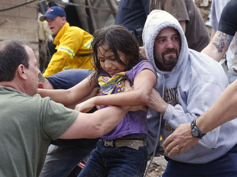 A child is passed along a human chain of people after being pulled from the rubble of the Plaza Towers Elementary School in Moore, Okla., and passed along a human chain of rescuers Monday, May 20, 2013. A tornado as much as a mile (1.6 kilometers) wide with winds up to 200 mph (320 kph) roared through the Oklahoma City suburbs Monday, flattening entire neighborhoods, setting buildings on fire and landing a direct blow on an elementary school. (AP Photo Sue Ogrocki) ORG XMIT: OKSO117
