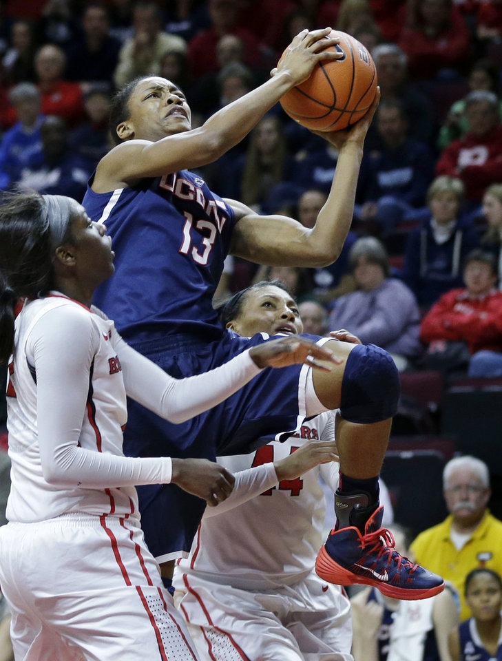 Photo - Connecticut guard Brianna Banks (13) takes a shot past Rutgers defenders, Betnijah Laney, right, and Kahleah Copper, left, during the second half of an NCAA women's college basketball game Sunday, Jan. 19, 2014, in Piscataway, N.J. Connecticut won 94-64. (AP Photo/Mel Evans)