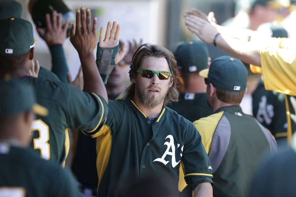 Photo - Oakland Athletics' Josh Reddick, center, is greeted by teammates after scoring off a single hit by Oakland Athletics' Derek Norris during the third inning of a spring training baseball game Monday, March 3, 2014, in Phoenix. (AP Photo/Gregory Bull)