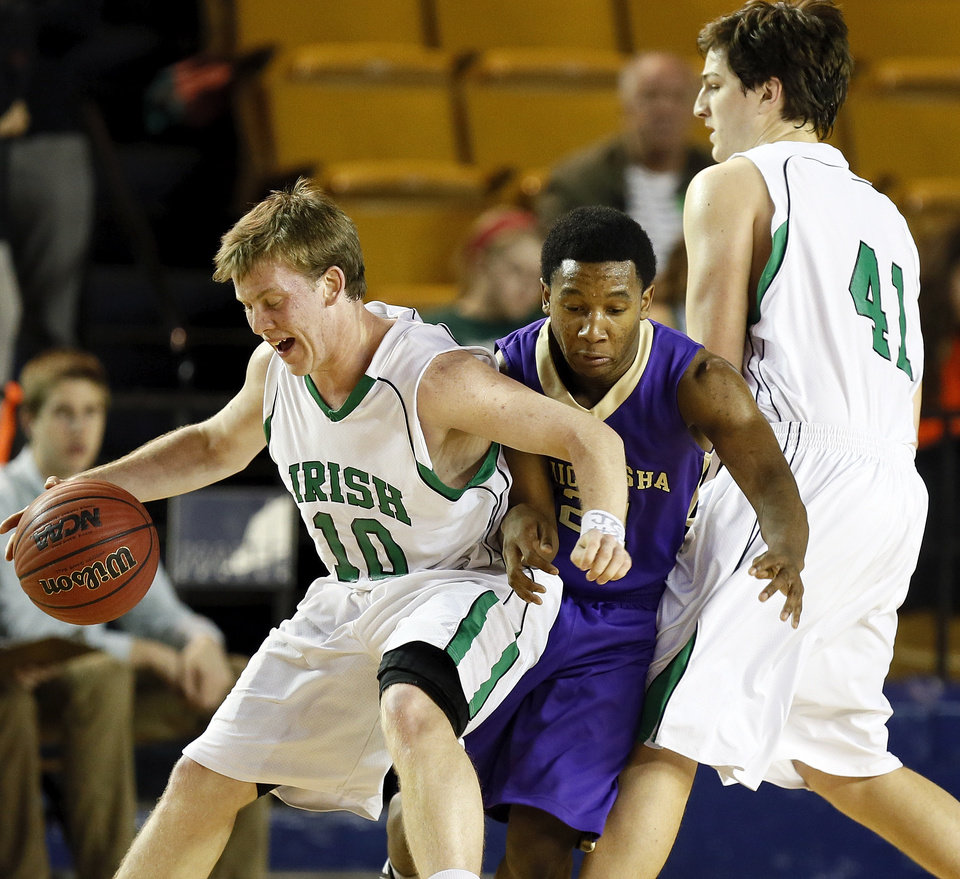 Bishop McGuinness\' Greg Roberts (10) tries to use a screen by David Love (41) to escape the defense of Chickasha\'s Deshawn Young (21) during a Class 5A boys high school basketball game in the semifinals of the state tournament at the Mabee Center in Tulsa, Okla., Friday, March 8, 2013. Bishop McGuinness beat Chickasha, 50-40. Photo by Nate Billings, The Oklahoman