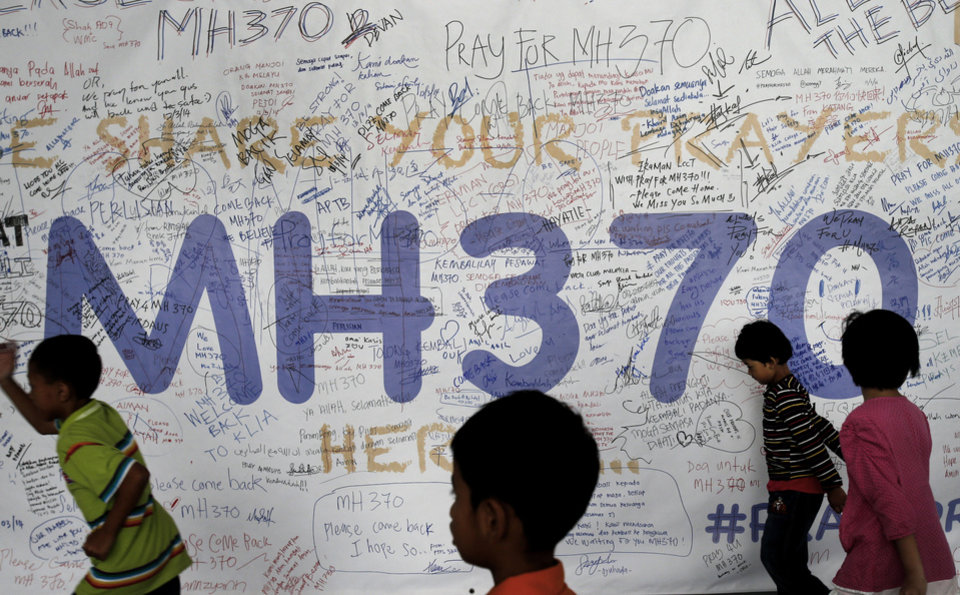 Photo - Children run past dedication messages and well wishes displayed for passengers and others involved with the missing Malaysia Airlines jetliner MH370 on the walls of the Kuala Lumpur International Airport, Thursday, March 13, 2014,  in Sepang, Malaysia. Planes sent Thursday to check the spot where Chinese satellite images showed possible debris from the missing Malaysian jetliner found nothing, Malaysia's civil aviation chief said, deflating the latest lead in the six-day hunt. The hunt for the missing Malaysia Airlines flight 370 has been punctuated by false leads since it disappeared with 239 people aboard about an hour after leaving Kuala Lumpur for Beijing early Saturday. (AP Photo/Wong Maye-E)