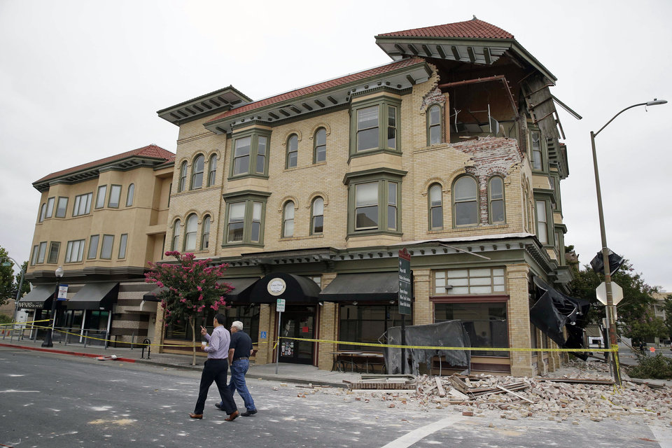Photo - Two men walk past the earthquake-damaged building that housed the Carpe Diem wine bar  Monday, Aug. 25, 2014, in Napa, Calif. The San Francisco Bay Area's strongest earthquake in 25 years struck the heart of California's wine country early Sunday, igniting gas-fed fires, damaging some of the region's famed wineries and historic buildings, and sending dozens of people to hospitals. (AP Photo/Eric Risberg)
