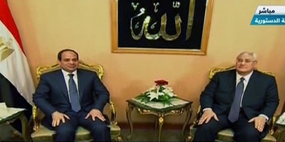 Photo - This image made from Egyptian State Television shows, soon to be sworn in President Abdel-Fattah el-Sissi, left, and outgoing interim President Adly Mansour at the Supreme Constitutional Court in Cairo, Egypt, Sunday, June 8, 2014. El-Sissi's inauguration Sunday comes less than a year after the 59-year-old career infantry officer ousted the country's first freely elected president, the Islamist Mohammed Morsi, following days of mass protests by Egyptians demanding he step down. (AP Photo/Egyptian State Television)
