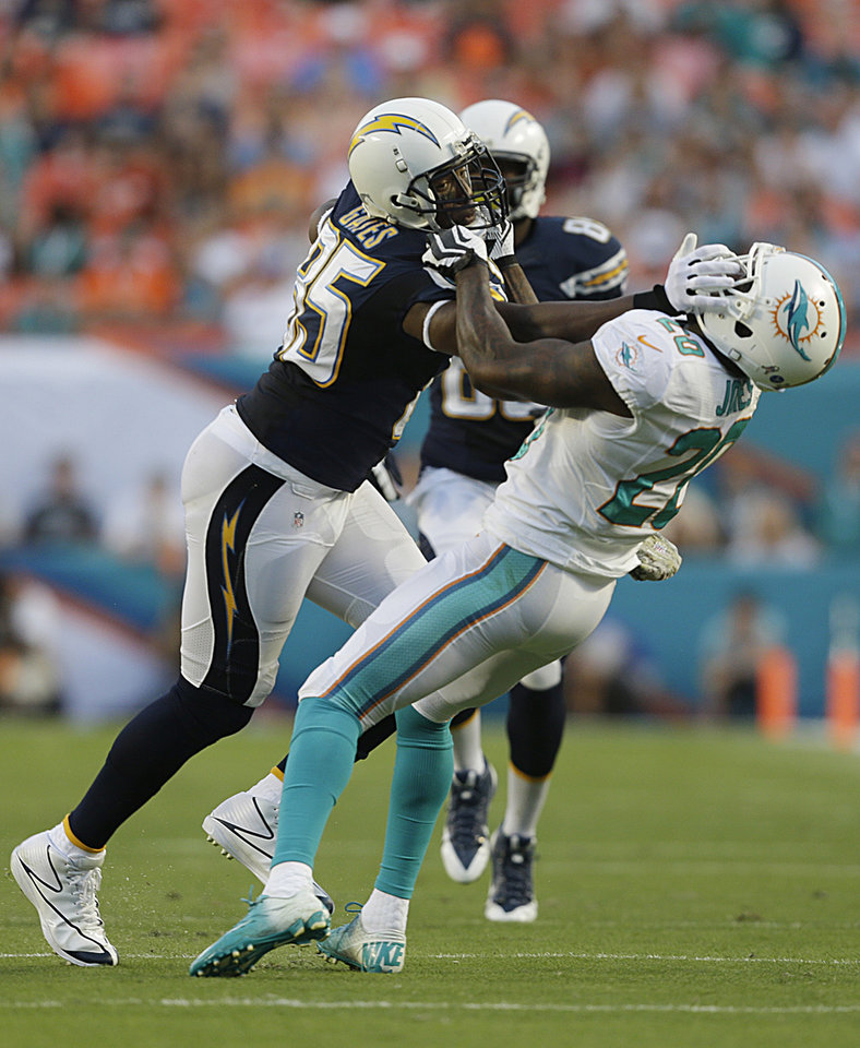 Photo - Miami Dolphins free safety Reshad Jones (20) attempts to bring down San Diego Chargers tight end Antonio Gates (85) during the first half of an NFL football game, Sunday, Nov. 17, 2013, in Miami Gardens, Fla. (AP Photo/Wilfredo Lee)