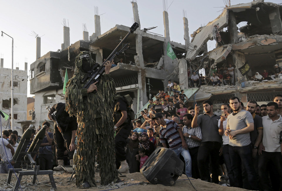 Photo - A Palestinian militant of Izzedine al-Qassam Brigades, military wing of Hamas, holds his rifle during a celebration of the victory rally at the debris of destroyed houses in Shijaiyah, neighborhood of Gaza City, in the northern Gaza Strip, Wednesday, Aug. 27, 2014. An open-ended cease-fire between Israel and Palestinian militants in the Gaza Strip was holding Wednesday. (AP Photo/Adel Hana)