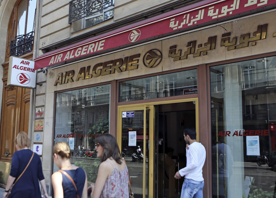 Photo - Passersby walk past the Air Algerie company office, on the Opera Avenue in Paris Thursday July 24, 2014. A flight operated by Air Algerie has disappeared from radar while traveling from Burkina Faso in West Africa to Algiers. Authorities say it was carrying over 100 passengers and crew when air navigation services lost track of the Swiftair plane 50 minutes after takeoff earlier Thursday morning. (AP Photo/Remy de la Mauviniere)