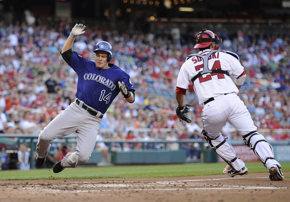 Colorado Rockies' Josh Rutledge (14) comes in to score on a single by DJ LeMahieu during the third inning of a baseball game against Washington Nationals catcher Kurt Suzuki (24), Friday, June 21, 2013, in Washington. (AP Photo/Nick Wass)