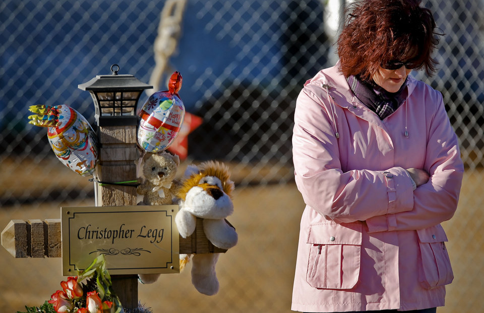 Photo - Tammy DeWitt takes a moment next to the cross of her nephew Christopher Legg while outside the Plaza Towers Elementary School during a balloon release to mark what would have been Legg's tenth birthday in Moore, Okla. on Thursday, Jan. 16, 2014. Christopher was killed along with six others when the May 20th tornado hit the school. Parents of those killed have been notified that the crosses will need to be removed for further rebuilding of the school. Photo by Chris Landsberger, The Oklahoman