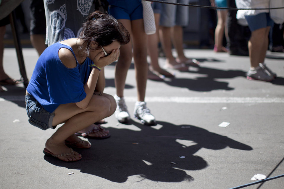 Photo - A girl cries in front of a makeshift memorial outside the Kiss nightclub where a fire killed over 230 people in Santa Maria, Brazil, Tuesday, Jan. 29, 2013. The repercussions of a tragic nightclub fire in southern Brazil widened Tuesday as mayors around the country cracked down on such venues in their own cities and investigators searched two other nightspots owned by a partner in the club that caught ablaze. Most of the dead were college students 18 to 21 years old, but they also included some minors.  (AP Photo/Felipe Dana)