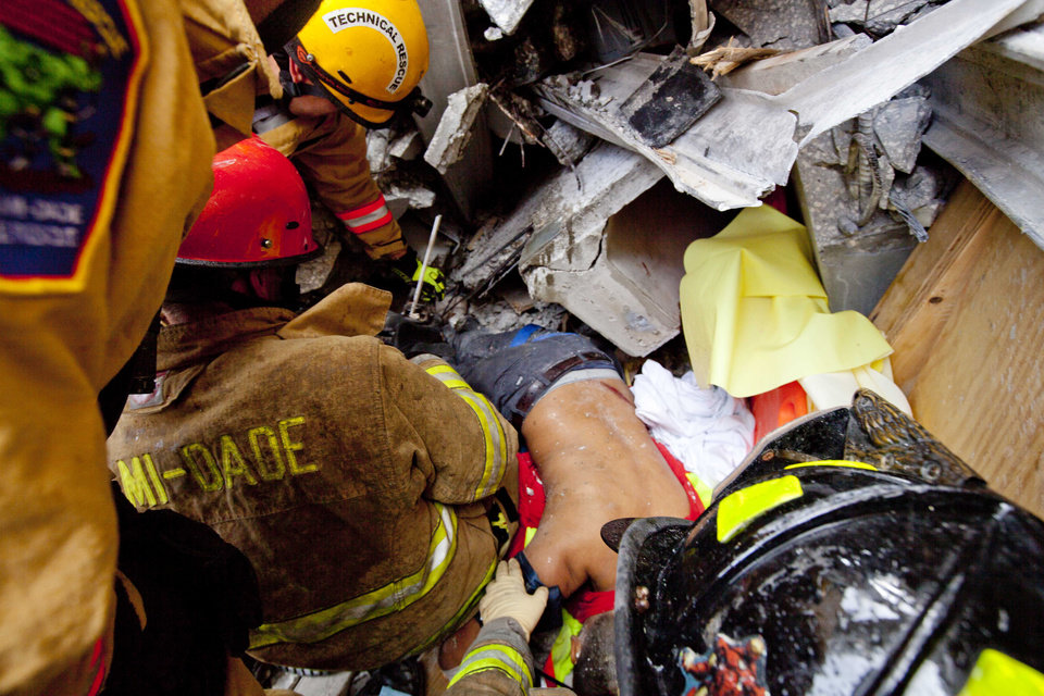Photo -   In this photo provided by Miami-Dade Fire Rescue, emergency workers remove an injured man from the rubble after a section of a parking garage under construction at a Miami-Dade College campus collapsed Wednesday, Oct. 10, 2012 in Doral, Fla., killing one worker and trapping at least two others in the rubble, officials said. (AP Photo/Miami-Dade Fire Rescue)