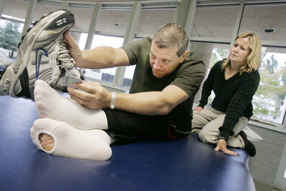 Photo - Before his death, Mark Hutchison worked relentlessly to recover from traumatic fall with physical therapist Kelli Holmes at the Jim Thorpe Rehabilitation Hospital.  JACONNA AGUIRRE - The Oklahoman