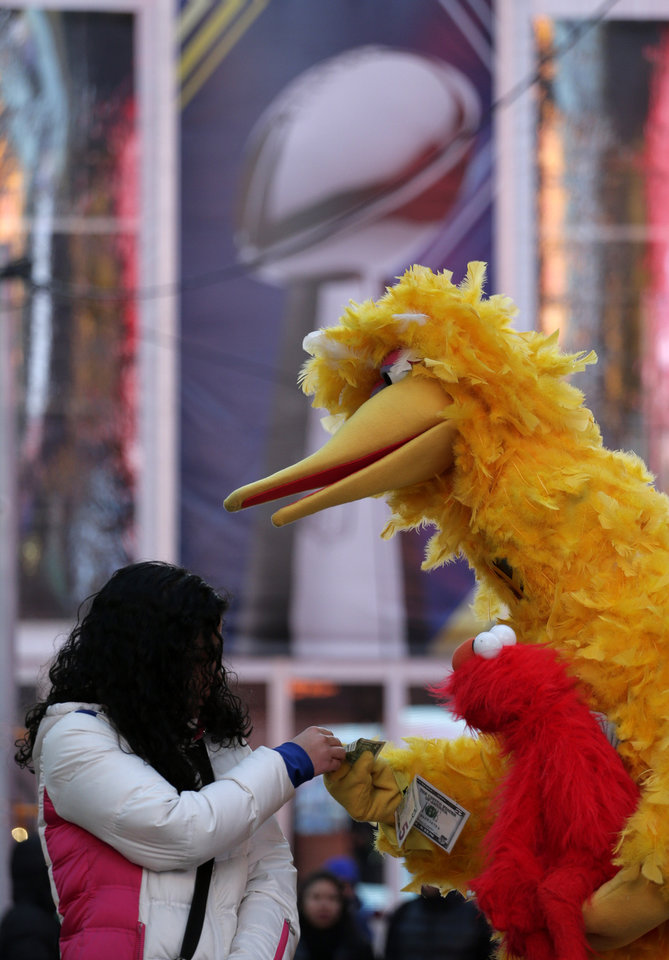 Photo - A street performer accepts a tip from a women in Times Square during Super Bowl Boulevard activities  Wednesday, Jan. 29, 2014, in New York. The Seattle Seahawks are scheduled to play the Denver Broncos in the NFL Super Bowl XLVIII football game on Sunday, Feb. 2, in East Rutherford, N.J. (AP Photo/Charlie Riedel)