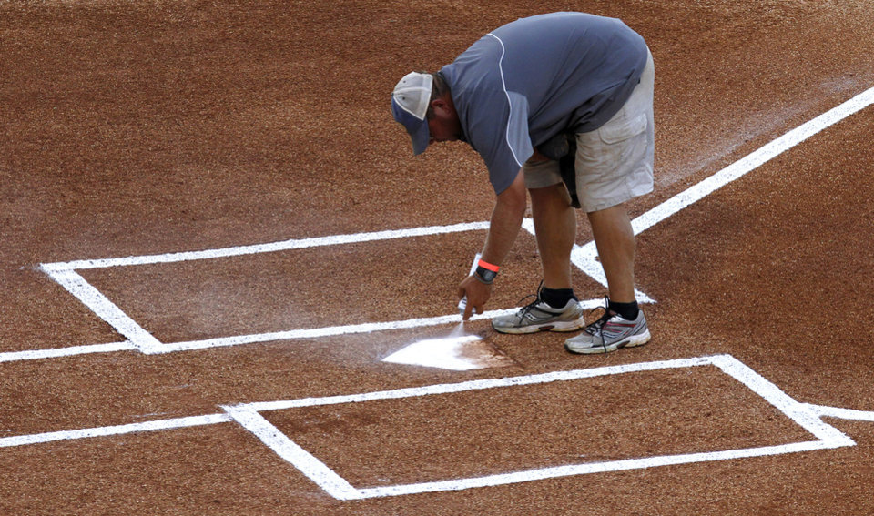 Photo - In this may 23, 2014 photo, Jeff Mondor, of Bradenton, Fla., spray paints home plate before a game at the Southeastern Conference NCAA college baseball tournament in Hoover, Ala. (AP Photo/Butch Dill)