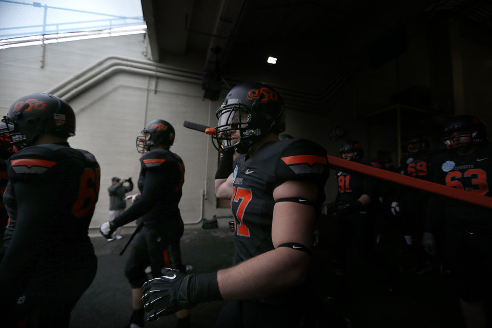 Photo - Oklahoma State's Alex Elkins (37)carries the big stick before the Heart of Dallas Bowl football game between the Oklahoma State University (OSU) and Purdue University at the Cotton Bowl in Dallas,  Tuesday,Jan. 1, 2013. Photo by Sarah Phipps, The Oklahoman